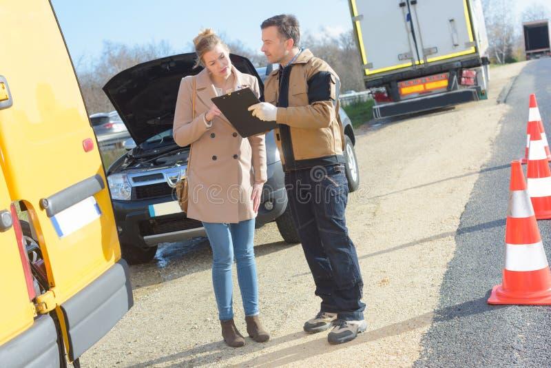 Giovane donna che parla con servizio dell'automobile di assistenza immagini stock libere da diritti