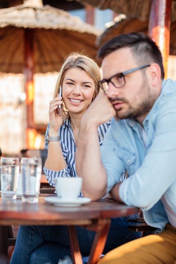 Giovane donna che parla sul telefono e che esamina il suo ragazzo che è annoiato ed infastidito fotografie stock libere da diritti