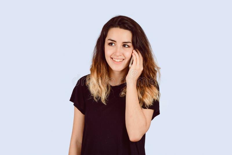 Giovane donna che parla sul telefono in uno studio fotografia stock libera da diritti