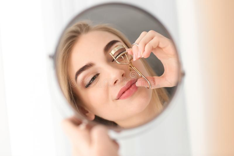 Giovane donna che per mezzo del bigodino del ciglio davanti allo specchio a casa immagine stock