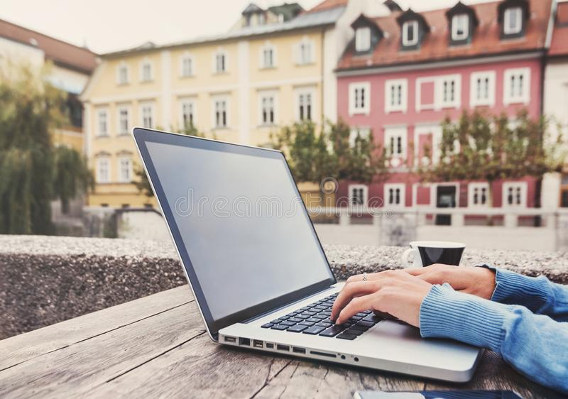 Giovane donna che per mezzo del computer portatile al caffè all'aperto Giovane bella ragazza che lavora al computer in una città fotografia stock