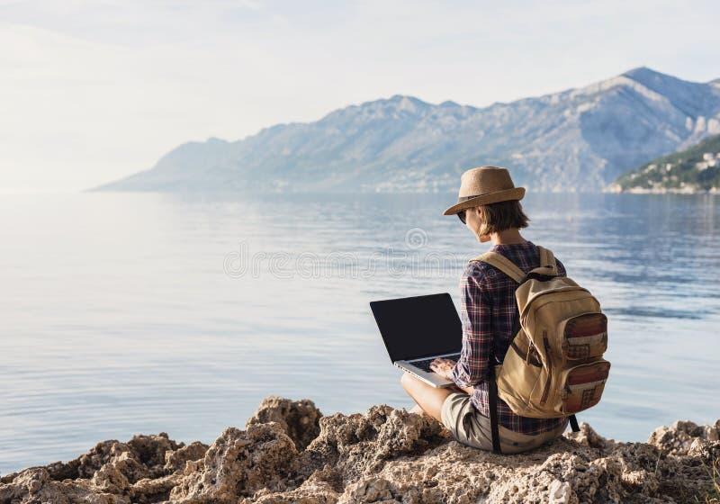 Giovane donna che per mezzo del computer portatile su un mare Freelance il concetto del lavoro immagini stock libere da diritti