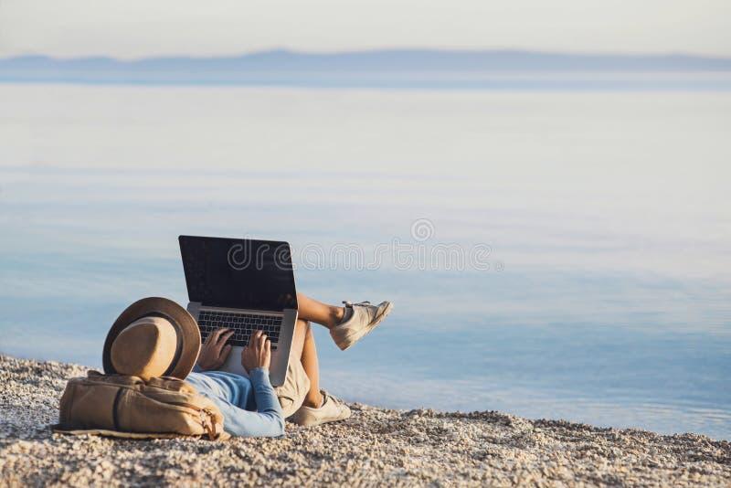 Giovane donna che per mezzo del computer portatile su una spiaggia Freelance il concetto del lavoro immagini stock