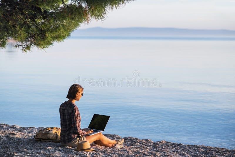 Giovane donna che per mezzo del computer portatile su una spiaggia Freelance il concetto del lavoro fotografia stock
