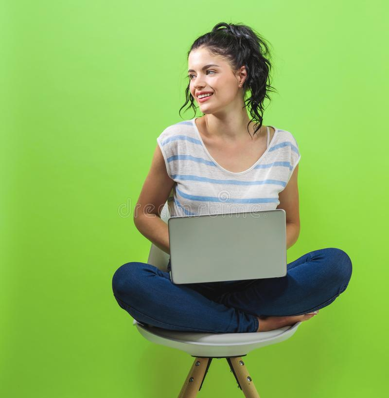 Giovane donna che per mezzo del suo computer portatile fotografie stock