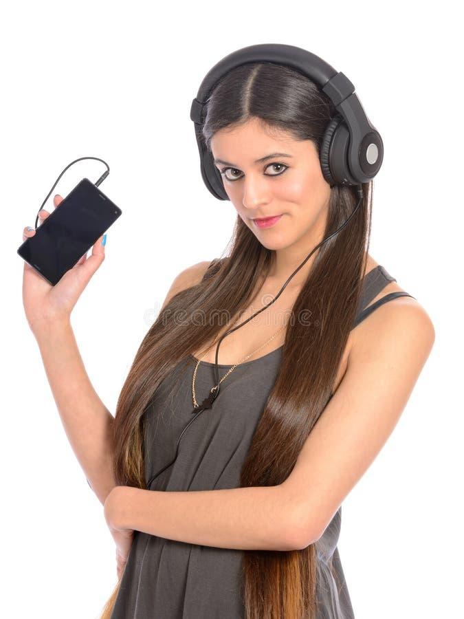 Giovane donna che per mezzo del telefono cellulare per ascoltare musica fotografia stock