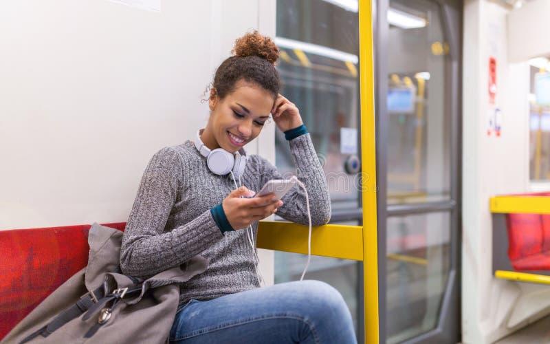 Giovane donna che per mezzo del telefono cellulare sul sottopassaggio fotografia stock
