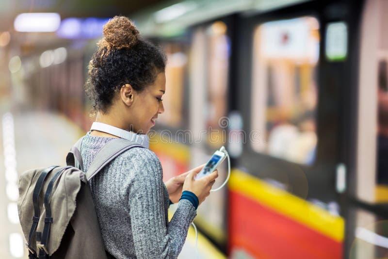 Giovane donna che per mezzo del telefono cellulare sul sottopassaggio immagine stock