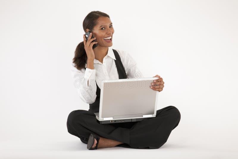 Giovane donna che per mezzo del telefono delle cellule e del computer portatile fotografia stock libera da diritti