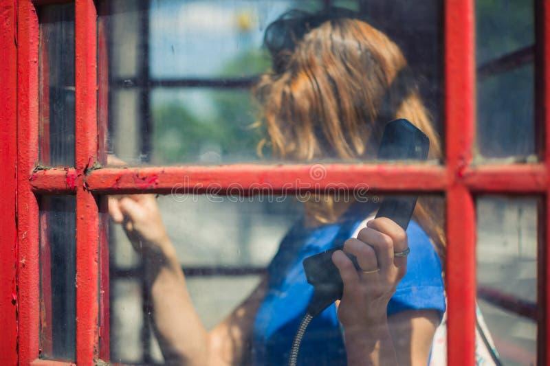 Giovane donna che per mezzo del telefono pubblico fotografia stock