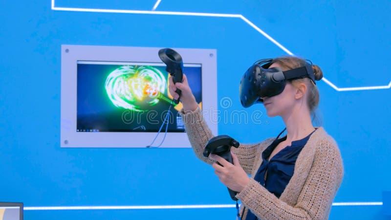 Giovane donna che per mezzo della cuffia avricolare di realtà virtuale e disegnando con la leva di comando speciale fotografie stock
