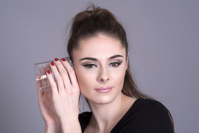 Giovane donna che per mezzo di un bicchiere come protesi acustica fotografie stock libere da diritti