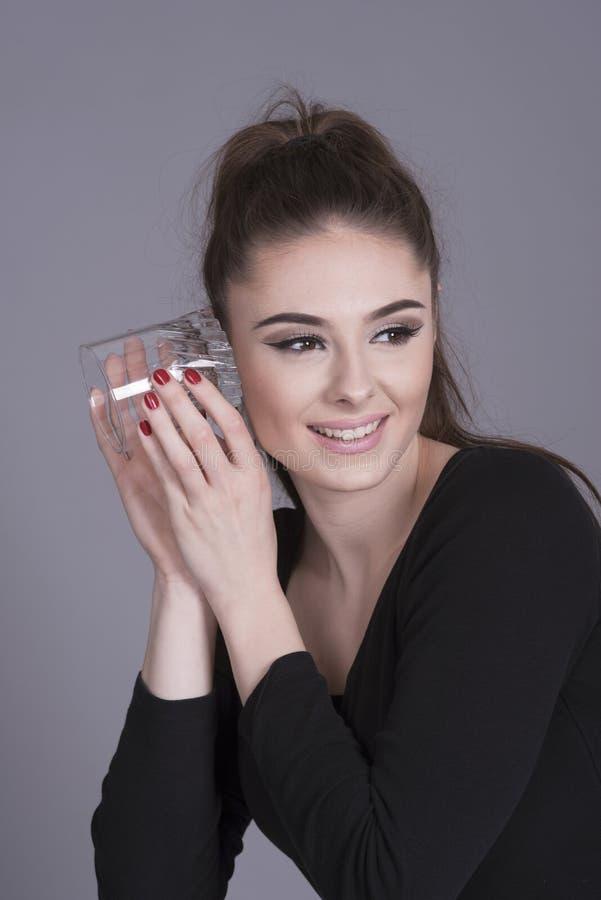 Giovane donna che per mezzo di un bicchiere come protesi acustica fotografia stock