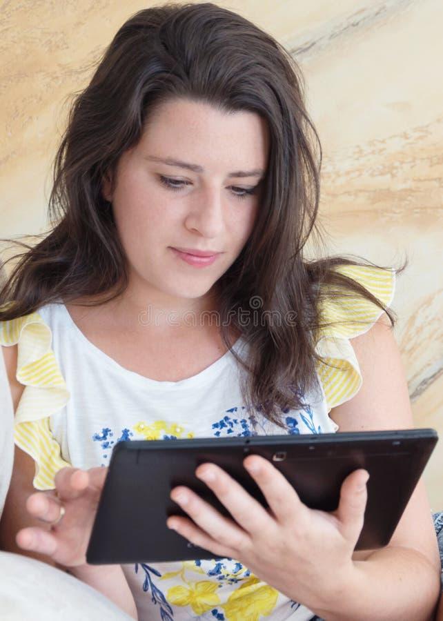 Giovane donna che per mezzo di un calcolatore del ridurre in pani immagini stock libere da diritti