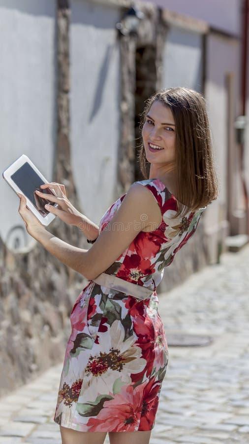 Giovane donna che per mezzo di una compressa immagini stock