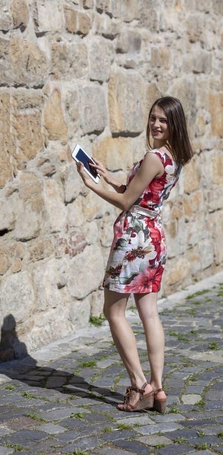 Giovane donna che per mezzo di una compressa fotografia stock
