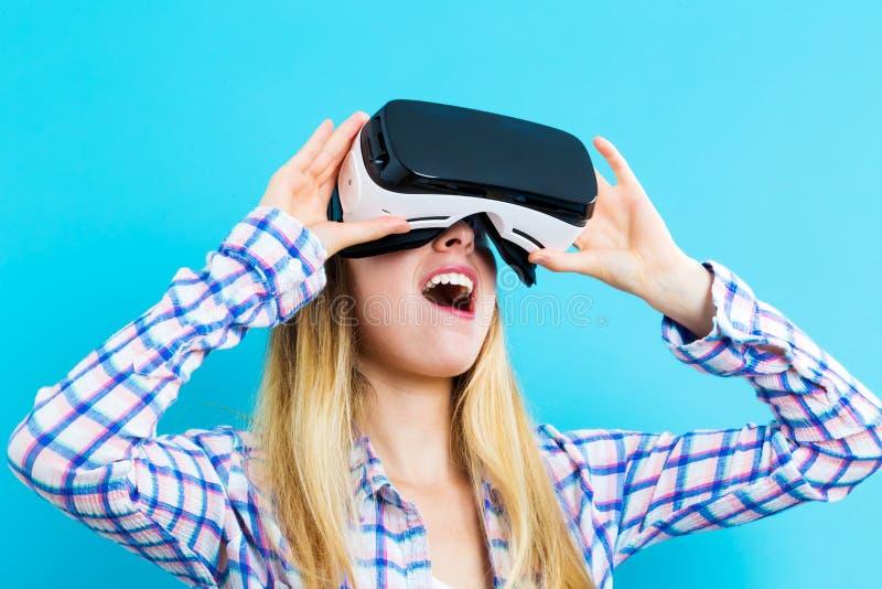 Giovane donna che per mezzo di una cuffia avricolare di realtà virtuale fotografie stock libere da diritti