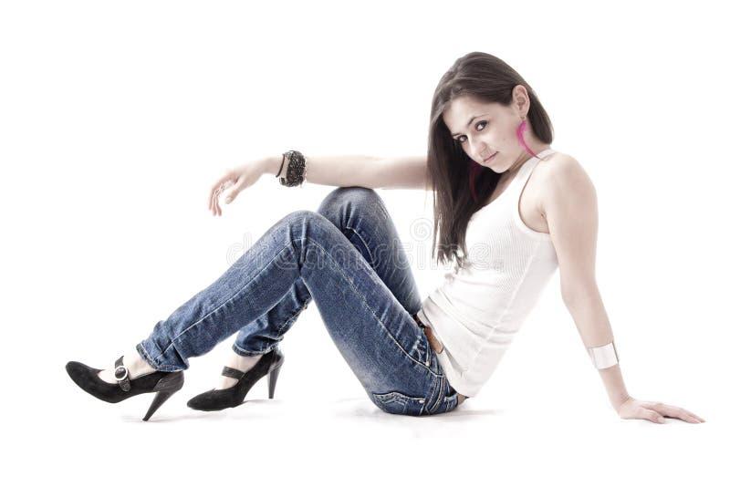 Giovane donna che pone sul pavimento, isolato fotografia stock libera da diritti