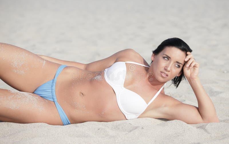Giovane donna che pone sulla sabbia immagini stock