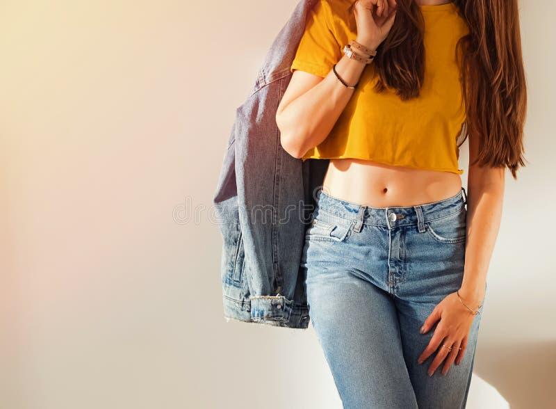 Giovane donna che porta maglietta ed i jeans gialli e che tiene il rivestimento del denim sulla sua spalla vicino alla parete bia fotografie stock