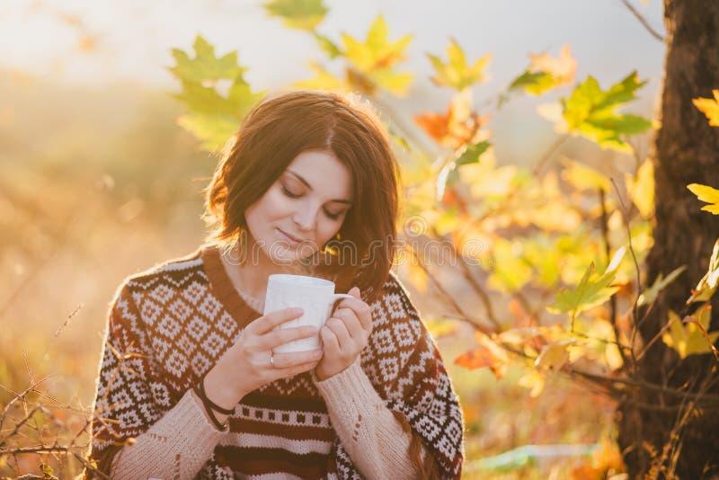 Giovane donna che porta poncio tricottato che ha picnic in una foresta: tè bevente e selezionare le mele fotografia stock