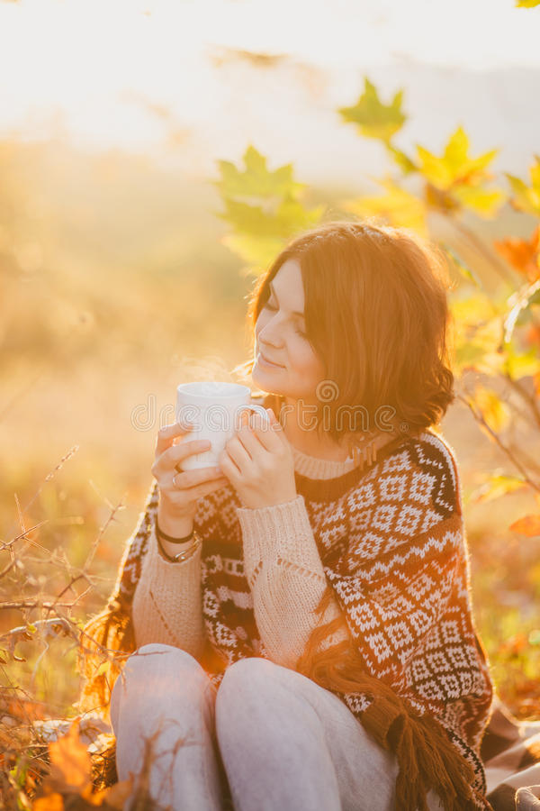 Giovane donna che porta poncio tricottato che ha picnic in una foresta: tè bevente e selezionare le mele fotografia stock libera da diritti