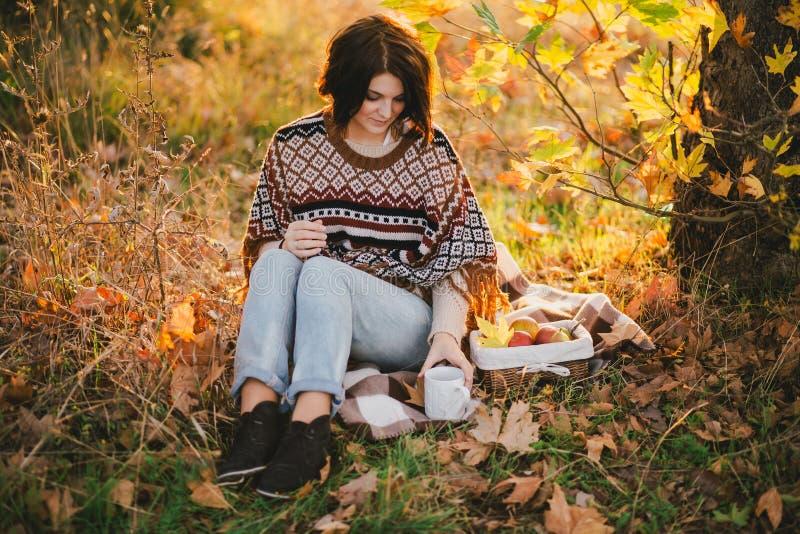 Giovane donna che porta poncio tricottato che ha picnic in una foresta: tè bevente e selezionare le mele fotografie stock libere da diritti
