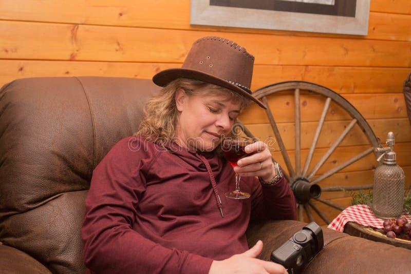 Giovane donna che porta un cappello marrone che giudica un vetro di vino rosso con lei occhi chiuso fotografia stock libera da diritti