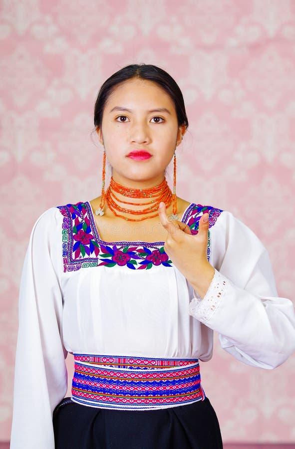 Giovane donna che porta vestito andino tradizionale, affrontante macchina fotografica che fa parola di linguaggio dei segni per l immagini stock libere da diritti