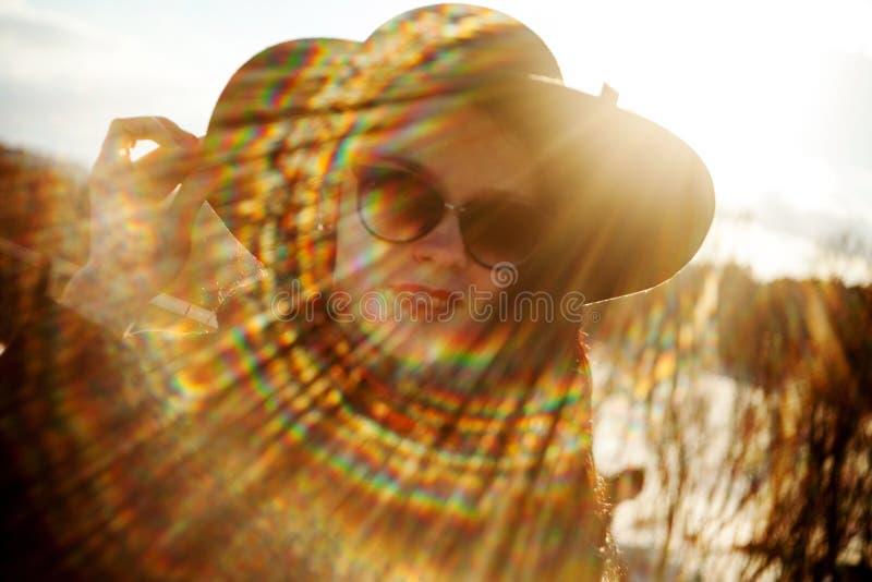 Giovane donna che posa in cappotto nero e black hat fotografia stock libera da diritti