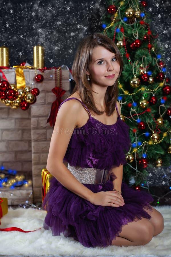 Giovane donna che posa davanti alla scena di Natale immagine stock libera da diritti