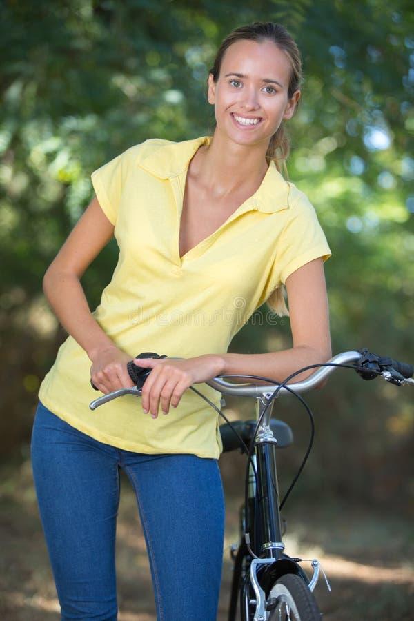 Giovane donna che posa mentre pendendo alla bici immagini stock libere da diritti