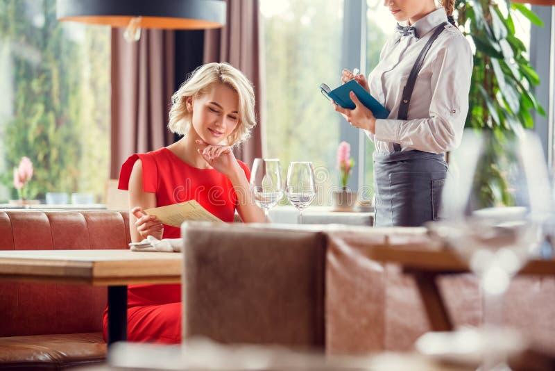 Giovane donna che pranza nel ristorante che si siede scegliendo piatto mentre ordine aspettante del cameriere fotografia stock