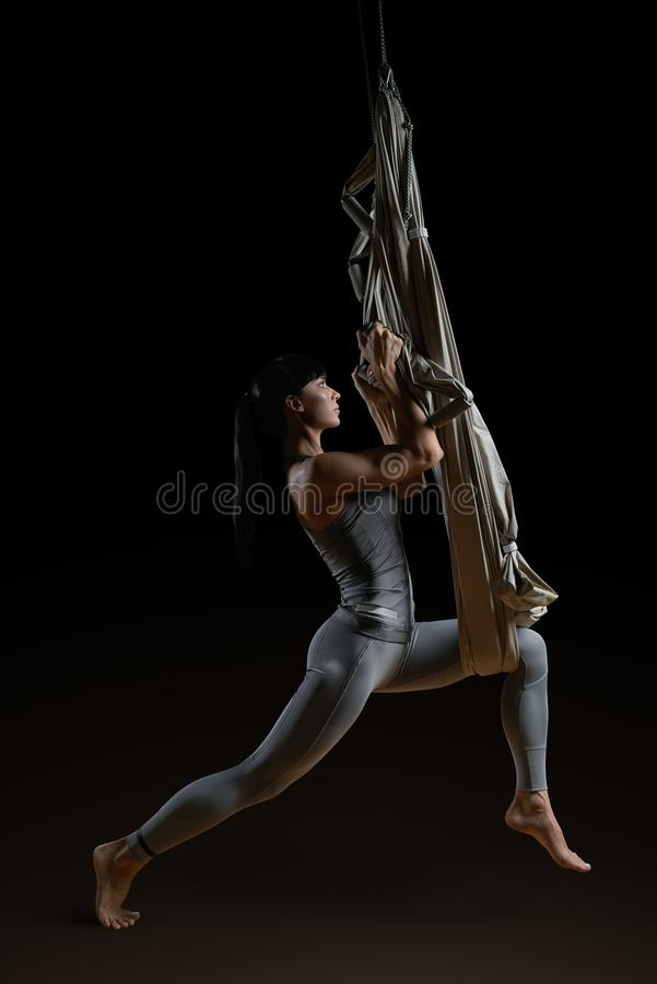 Giovane donna che pratica l'amaca aerea di yoga immagini stock libere da diritti