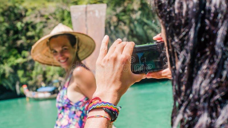 Giovane donna che prende foto del suo amico alla barca immagini stock libere da diritti