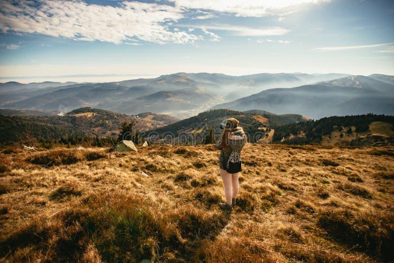 Giovane donna che prende immagine di una valle nebbiosa immagini stock libere da diritti