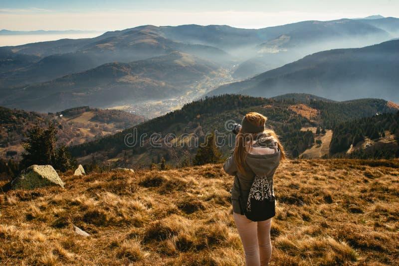 Giovane donna che prende immagine di una valle nebbiosa immagine stock libera da diritti
