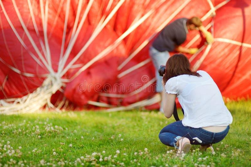 Giovane donna che prende le foto dei palloni fotografia stock