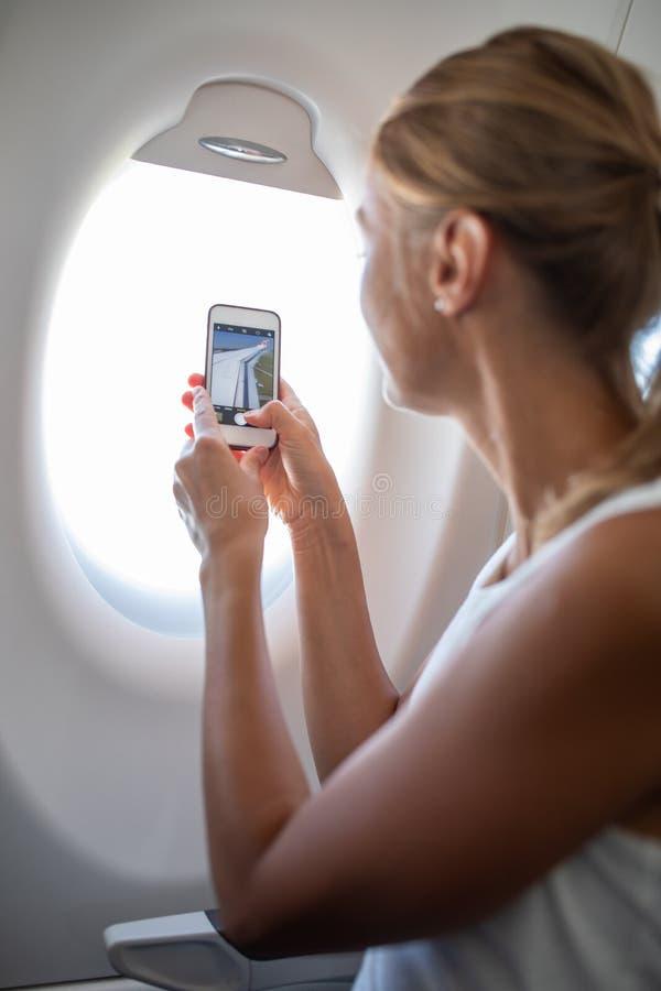 Giovane donna che prende le foto durante il volo immagine stock