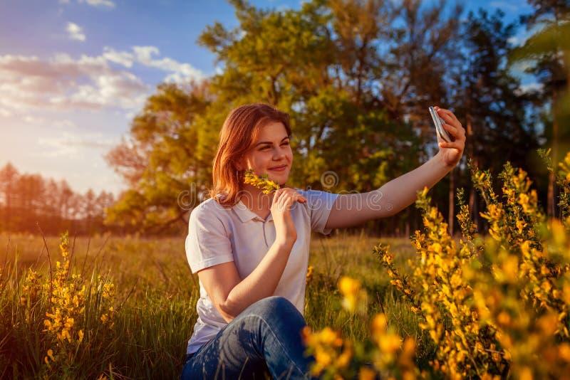 Giovane donna che prende selfie nel giacimento di fioritura di primavera al tramonto La ragazza sorridente felice si rilassa e go fotografia stock