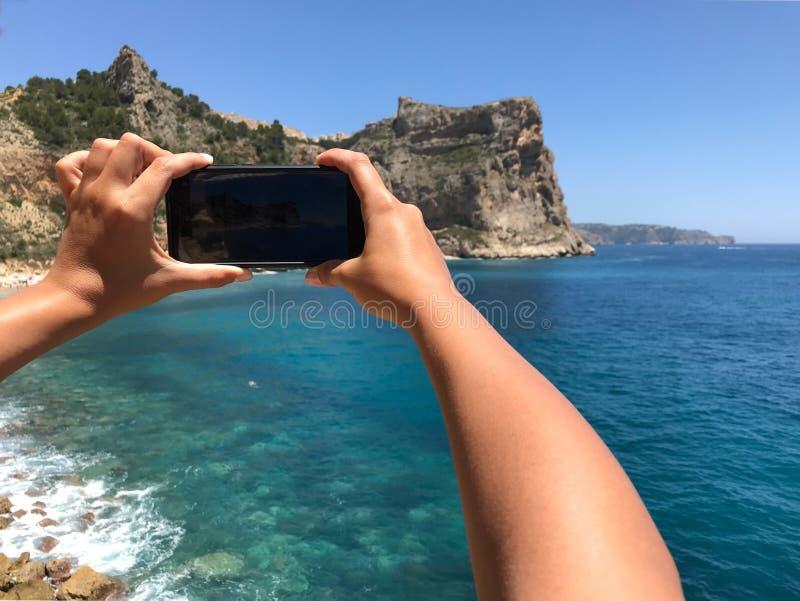 Giovane donna che prende un'immagine sulla spiaggia con un telefono cellulare fotografia stock