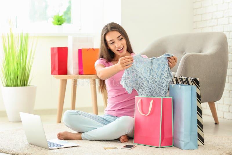 Giovane donna che prende vestito dal sacchetto della spesa a casa fotografia stock libera da diritti