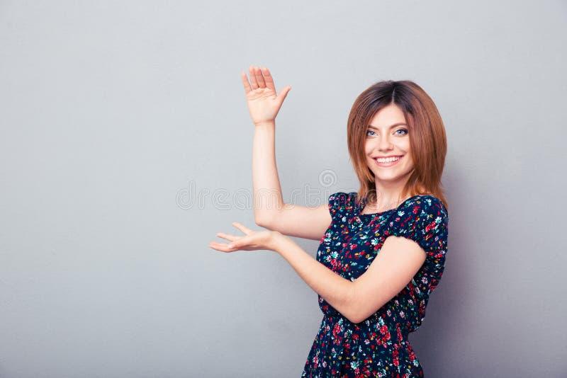 Giovane donna che presenta qualcosa sulle palme immagini stock