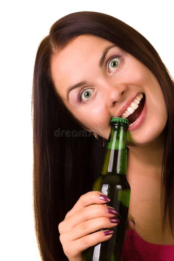 Giovane donna che prova ad aprire una bottiglia di birra fotografie stock