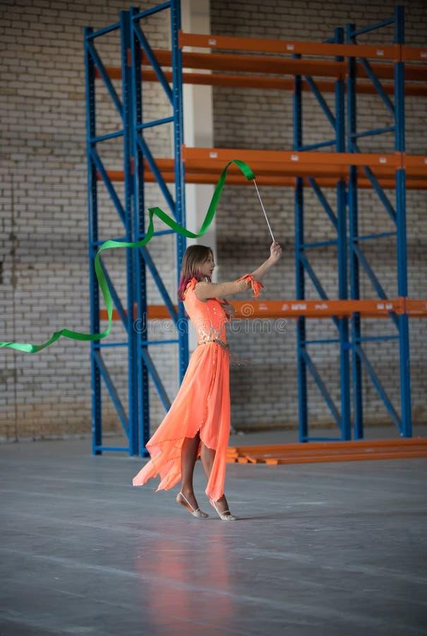 Giovane donna che resta con il nastro relativo alla ginnastica in mani dell'interno fotografia stock libera da diritti