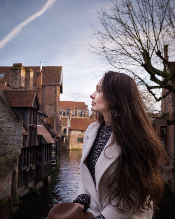 Giovane donna che resta nel posto romantico con le costruzioni d'annata fotografia stock libera da diritti