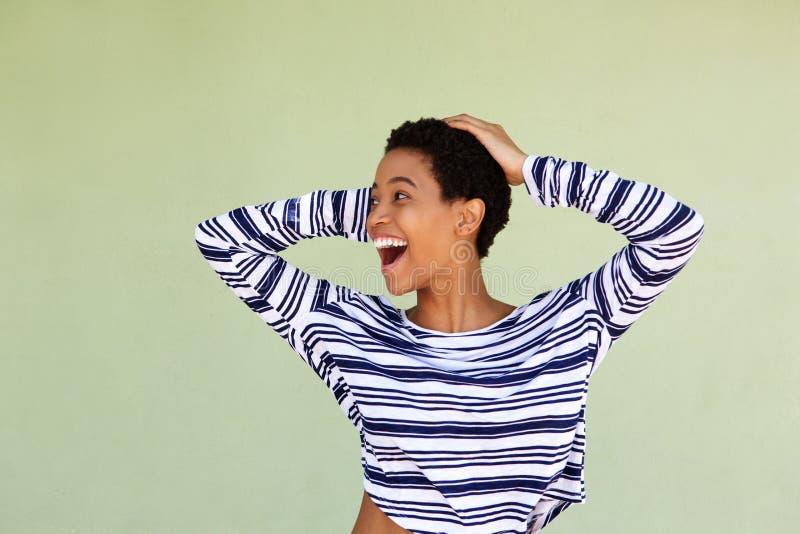 Giovane donna che ride con la mano in capelli contro il fondo verde fotografie stock