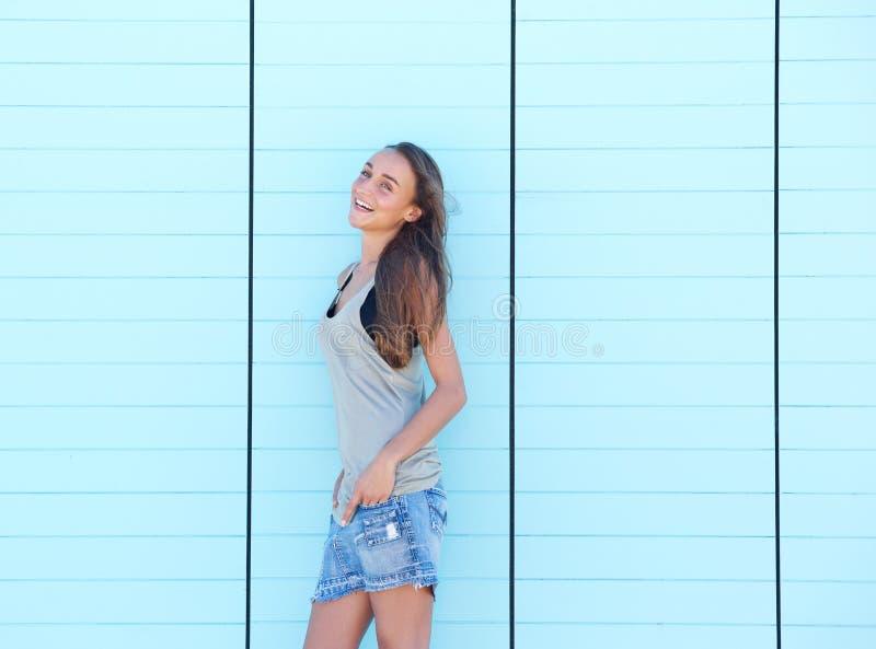 Giovane donna che ride contro il fondo blu fotografia stock