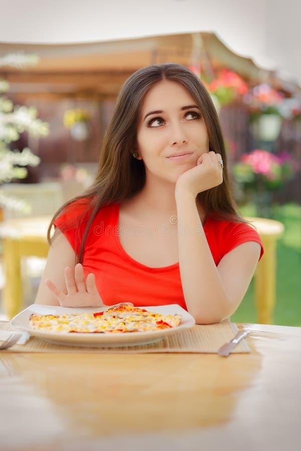 Giovane donna che rifiuta di mangiare una pizza fotografie stock libere da diritti