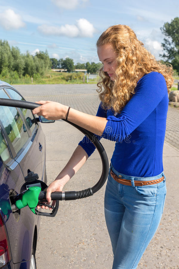 Giovane donna che rifornisce il carro armato di combustibile dell'automobile con benzina immagini stock libere da diritti